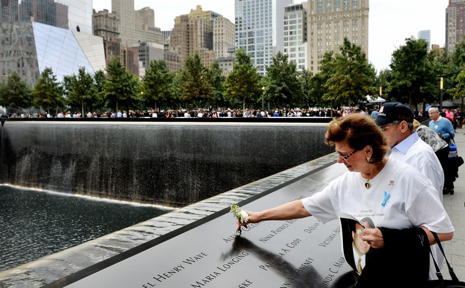 Maria Cioccone, of New York, places a flower in the inscribed name of her son Alex along the edge of the North Pool during memorial observances on the 13th anniversary of the Sept. 11 terror attacks on the World Trade Center in New York, Thursday, Sept. 1