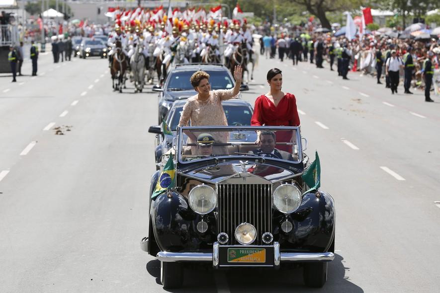 Sob o veículo oficial, Dilma Rousseff, ao lado de sua filha Paula, acena para a muiltidão presente na Esplanada dos Ministérios