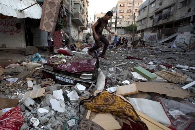 Palestino pula sobre caro ao avaliar os estragos causados por disparos israelenses nesta quinta-feira (10) (Foto: Mohammed Abed/AFP)