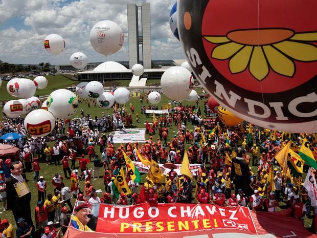 Trabalhadores se reúnem para uma homenagem ao presidente da Venezuela, Hugo Chávez, durante uma marcha em Brasília. (Foto: Eraldo Peres/AP)