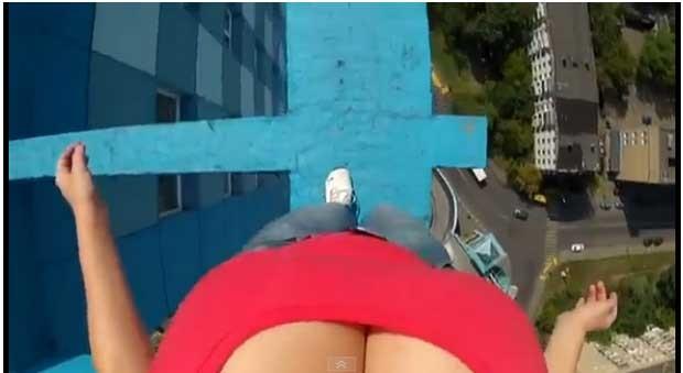 Cena de vídeo em que decotada se equilibra no topo de prédio (Foto: Reprodução)