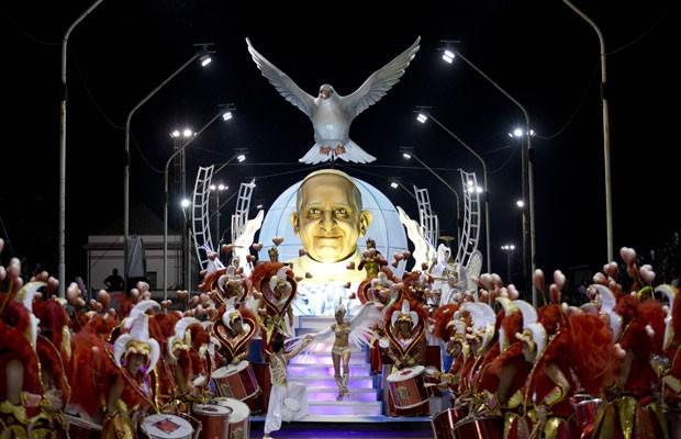 Foliões pulam o Carnaval em frente a carro alegórico com rosto do Papa Francisco, da escola de samba argentina Ara Yevi, que teve o sumo pontífice da Igreja Católica como tema em 2015. (Foto: Natacha PIsarenko/AP)