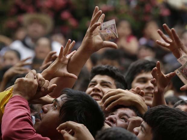 Meninos disputam nota equivalente a US$ 0,40 jogada de igreja da cidade de Guarambaré (Foto: AP Photo/Jorge Saenz)