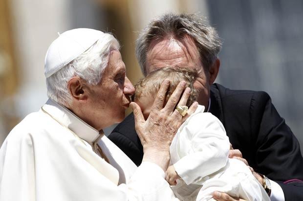 O Papa Bento XVI beija criança durante audiência no Vaticano nesta quarta-feira (30) (Foto: AFP)
