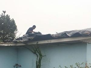 Morador coloca lona sobre o telhado para amenizar os efeitos da chuva (Foto: Cleberton de Aguiar Ribeiro / RBS TV)
