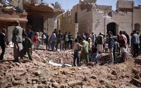 Um grupo de civis observa uma cratera aberta por um bombardeio saudita em Sanaa, capital do Iêmen (Foto: AP)