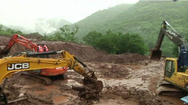 Equipes trabalham em local onde antes havia casas (Foto: BBC)