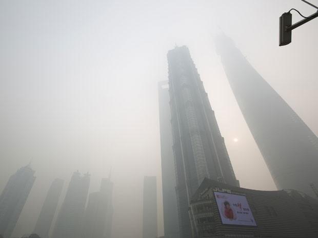 Um telão e edifícios vistos em meio à poluição pesada no distrito financeiro de Pudong em Xangai no dia 6/12/13 (Foto: Aly Song/Reuters)