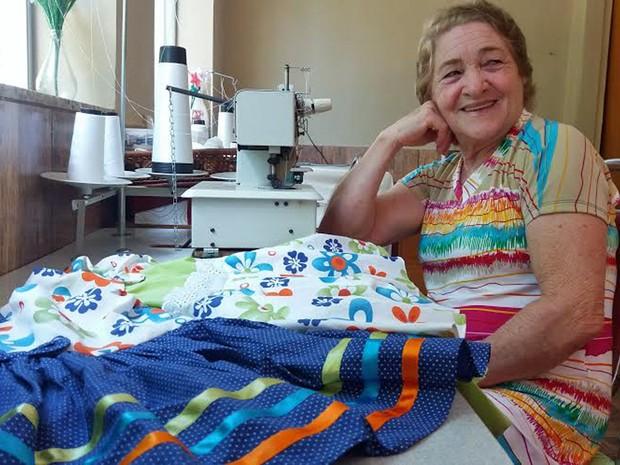 A costureira Rita Machado, de 69 anos, mostra alguns vestidos que vende na web (Foto: Verônica Machado)