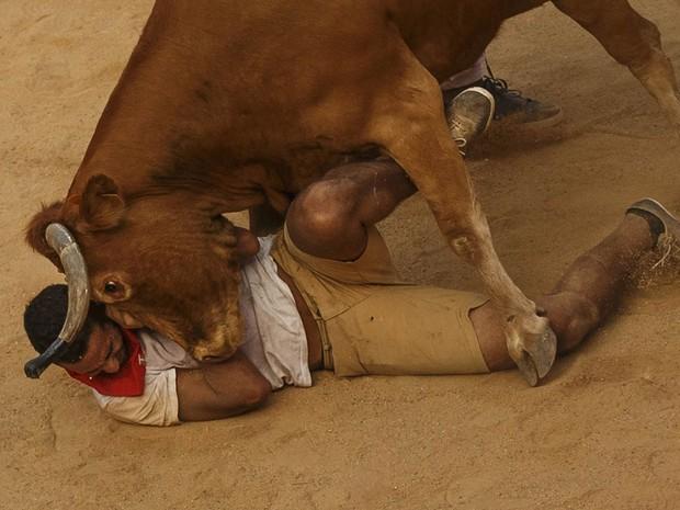 Folião fica face a face com uma vaca na arena de touradas de Pamplona, ponto de chegada da corrida de touros que corta a cidade diariamente durante 8 dias do Festival de São Firmino, na Espanha (Foto: Daniel Ochoa de Olza/AP)