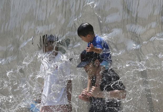 Japoneses se refrescam em fonte no último sábado (26) em Tóquio. Pelo menos 15 pessoas morreram durante onda de calor no país (Foto: Koji Sasahara/AP)