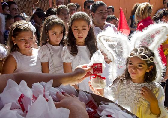 Um anjinho que participou do Cortejo das Virgens recebe um pacote com três Verônicas (Foto: Haroldo Castro/Época)