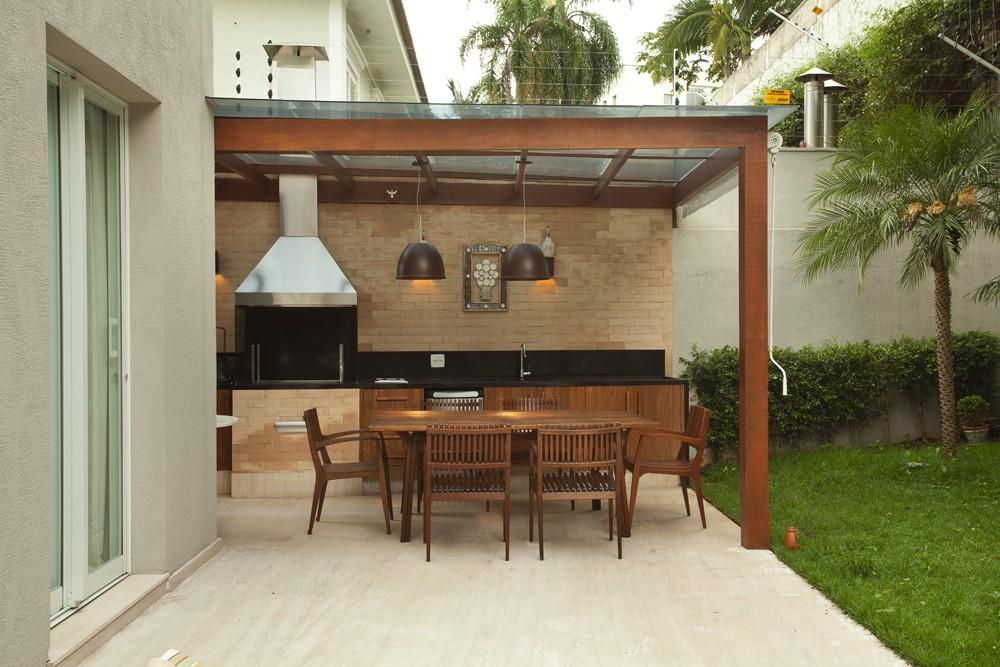 Um pergolado coberto protege a varanda gourmet. Churrasqueira, da Lazer & Cia. Tijolos aparentes, da Lepri. Luminárias, da La Lampe  (Foto: Adriana Barbosa/Divulgação)