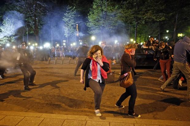 Mulheres correm de bomba de gás lacrimogênio durante protesto (Foto: Benoit Tessier/Reuters)