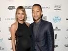 Chrissy Teigen, grávida, usa vestido justo e dispensa lingerie para festa