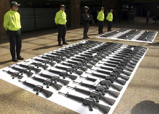 Policiais guardam nesta segunda-feira (23) em Bogotá parte do arsenal que, segundo as autoridades, seria destinado às Farc (Foto: AP)