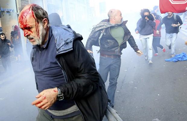 Homem ferido em protesto corre com outras pessoas entre fumaça de gás lacrimogêneo em Roma (Foto: Alessandro Bianchi/Reuters)