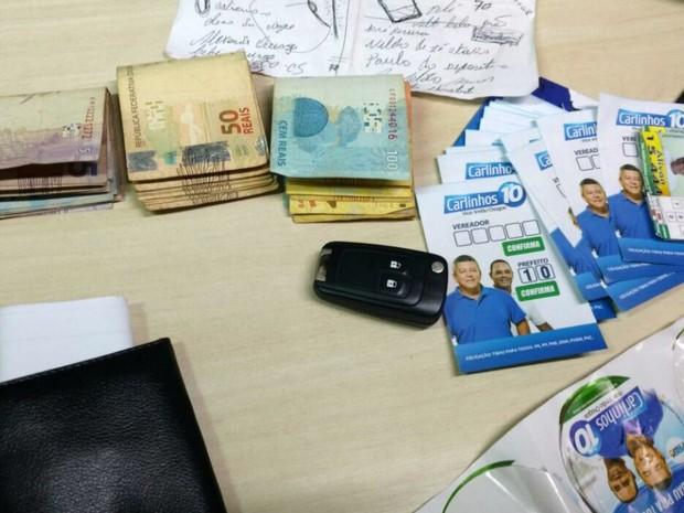 """Dinheiro e """"santinhos"""" foram apreendidos com dois homens em Tibau, RN (Foto: Divulgação/PM)"""
