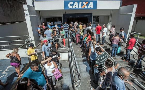 Trabalhadores fazem filas para retirar dinheiro que  estava parada.Os recursos devem ajudar a equilibrar o orçamento das famílias (Foto: Rogério Cassimiro/ÉPOCA)