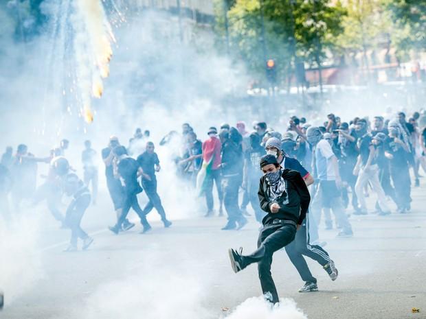 Manifestantes contrários à ofensiva israelense tentam chutar de volta as bombas de gás lacrimogêneo contra a polícia em Paris (Foto: Benjamin Girette/AP)
