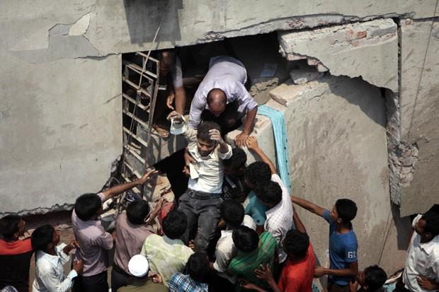 Pessoas ajudam a retirar um homem que estava dentro do prédio no momento do desabamento em Savar (Foto: A.M. Ahad/AP)