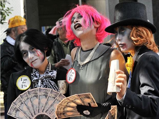 Ativistas japoneses anti-globalização protestam contra uma reunião do Fundo Monetário Internacional (FMI) realizada neste sábado em Tóquio, no Japão. Com máscaras e fantasias, eles se manifestaram contra o poder do dinheiro. (Foto: Rie ISHII/AFP)