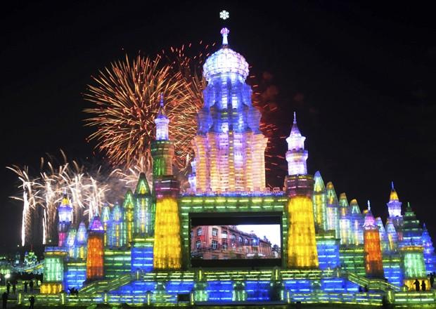 Turistas observam fogos de artifício sobre esculturas de gelo durante a abertura oficial do Festival de Gelo de Harbin, na província chinesa de Heilongjiang. A celebração, realizada na cidade do nordeste da China, é famosa pelas esculturas de castelos e objetos e artistas construídas com neve e gelo (Foto: China Daily/Reuters)