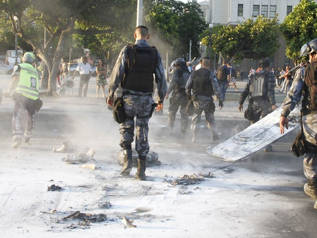 Policiais caminham em meio ao pó de extintores de incêndio depois que o fogo em uma barricada de pneus foi apagado no Centro do Rio (Foto: Onofre Veras/Agência O Dia/Estadão Conteúdo)