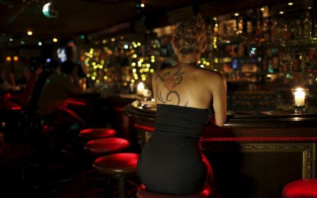 Mulher aguarda no balcão do bar da casa noturna Pascha em Salzburgo, na Áustria (Foto: Leonhard Foeger/Reuters)