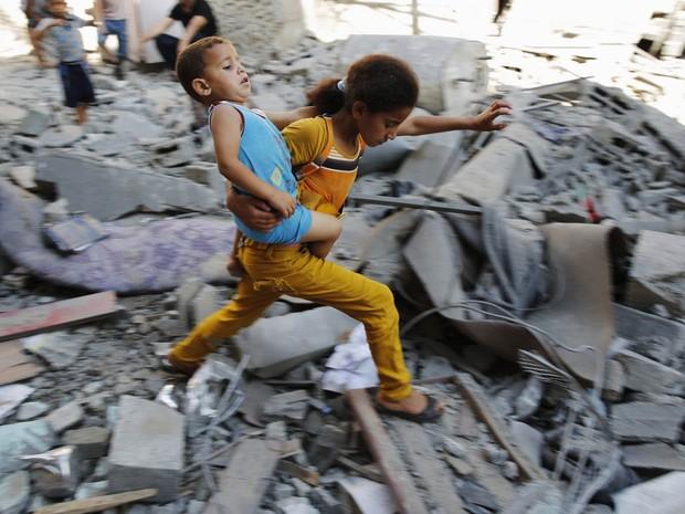 1º/8 - Com uma criança no colo, menina palestina atravessa destroços de um prédio atingido por bombardeio no campo de refugiados de Burij, na região central de Gaza (Foto: Finbarr O'Reilly/Reuters)