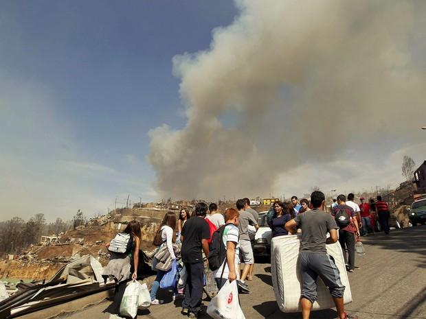 Moradores carregam pertences após incêndio que atingiu Valparaíso no sábado; 11 pessoas morreram e 10 mil ficaram desabrigadas (Foto: Reuters/Eliseo Fernandez)