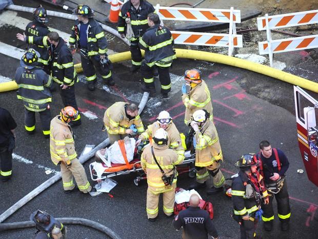 Bombeiros prestam socorro a uma pessoa ferida na explosão que atingiu prédios em East Village, em Nova York (Foto: Louis Lanzano/AP)