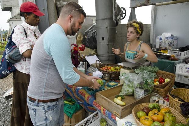 A vendedora do mercado semanal oferece pimentões, pepinos e tomates aos visitantes de sábado (Foto: Haroldo Castro/ÉPOCA)
