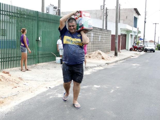 Valetin Rossi carrega água em lata e repete o trajeto até cinco vezes ao dia (Foto: Fabio Rodrigues/G1)