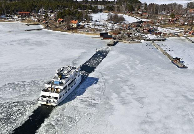 Navio utiliza canal aberto por navio quebra-gelo no mar Báltico, na Suécia (Foto: Anders Wiklund/Scanpix Sweden/AP)