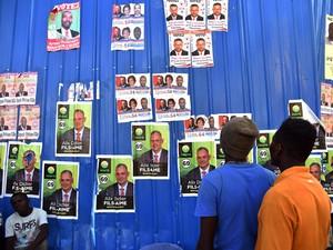 Eleitores observam propagandas de candidatos a deputado em Petion Ville, em Porto Príncipe, no Haiti, na quarta (5) (Foto: AFP Photo/Hector Retamal)