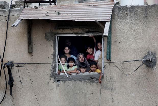Família palestina vê resgate de corpos de vítimas de bombardeios na cidade de Gaza nesta segunda-feira (21) (Foto: Khalil Hamra/AP)