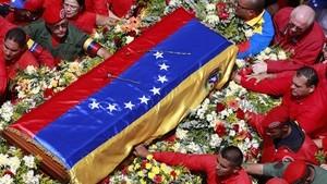 Mãe chora apoiada ao caixão ao som do hino no cortejo fúnebre de Chávez (Ricardo Mazalan/AP)