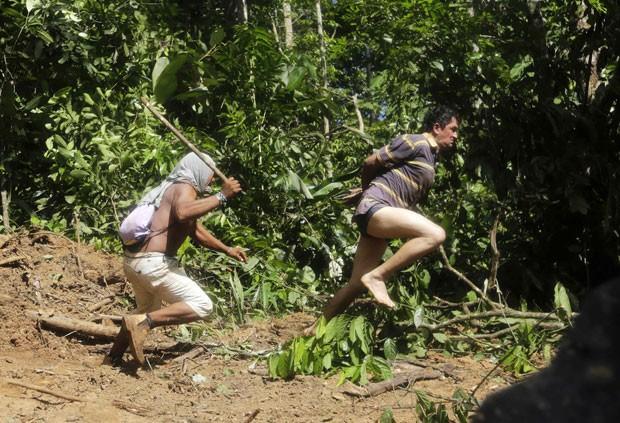 Guerreiro indígena tenta capturar madeireiro que fugiu durante operação independente feita pela tribo Ka'apor, no Maranhão (Foto: Lunaé Parracho/Reuters)