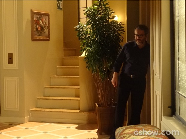 Nando fica atrás da porta ouvindo a briga do casal (Foto: Em Família / TV Globo)