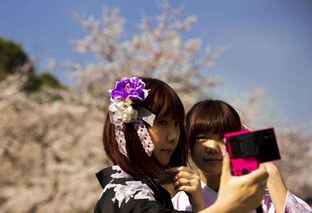 Japonesas no parque Ueno, em Tóquio, admiram a floração plena das cerejeiras no dia 30/3 (Foto: Thomas Peter/Reuters)