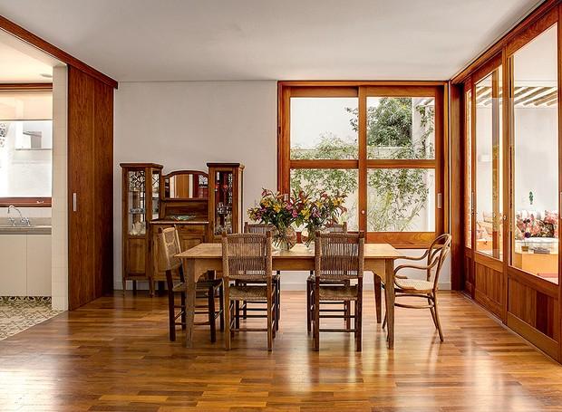 Os moradores queriam o clima de interior, mesmo estando em São Paulo. O arquiteto Carlos Verna fez uma casa com muita madeira, inclusive na sala de jantar. Ampla, ela é integrada com o jardim e a cozinha com portas de correr (Foto: Edu Castello/Casa e Jardim)