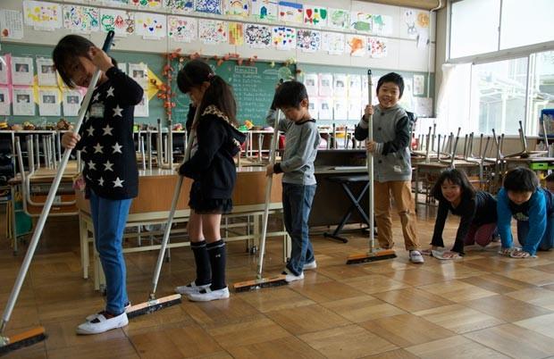 Reunidos em grupos, alunos se revezam na tarefa de limpar a escola no Japão. (Foto: Marcelo Hide/BBC)