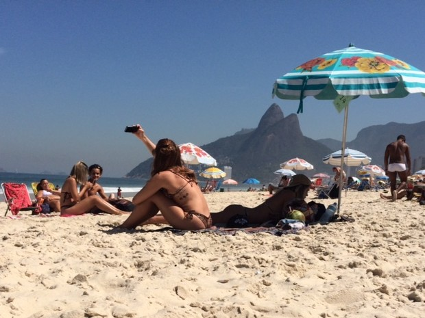 Menina aproveita dia de sol para tirar selfie na praia de Ipanema, no Rio (Foto: Matheus Rodrigues/ G1)