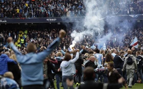 Torcedores do Manchester City invadem campo para comemorar. Clube conquistou o título do Campeonato Inglês (Foto: Jon Super/AP)