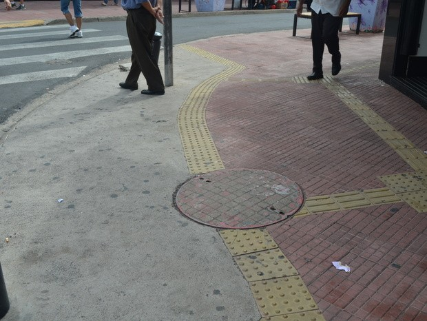 Tampa de bueiro interrompe piso tátil em rua no centro de Piracicaba (Foto: Fernanda Zanetti/G1)