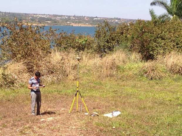 Técnico calcula distância a ser liberada na orla do Lago Paranoá, em Brasília (Foto: Gabriel Luiz/G1)