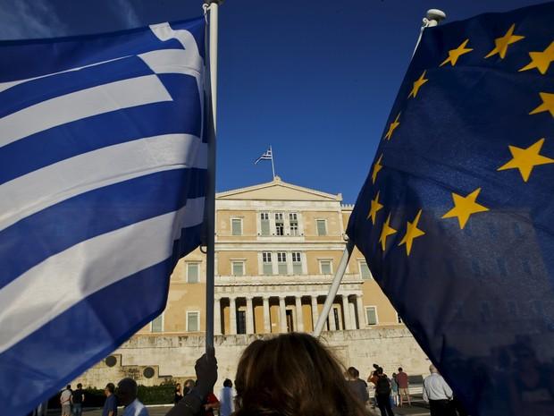 Bandeiras grega e da União Europeia em frente ao parlamento em Atenas, nesta quinta-feira (18) (Foto: Reuters/Yannis Behrakis)