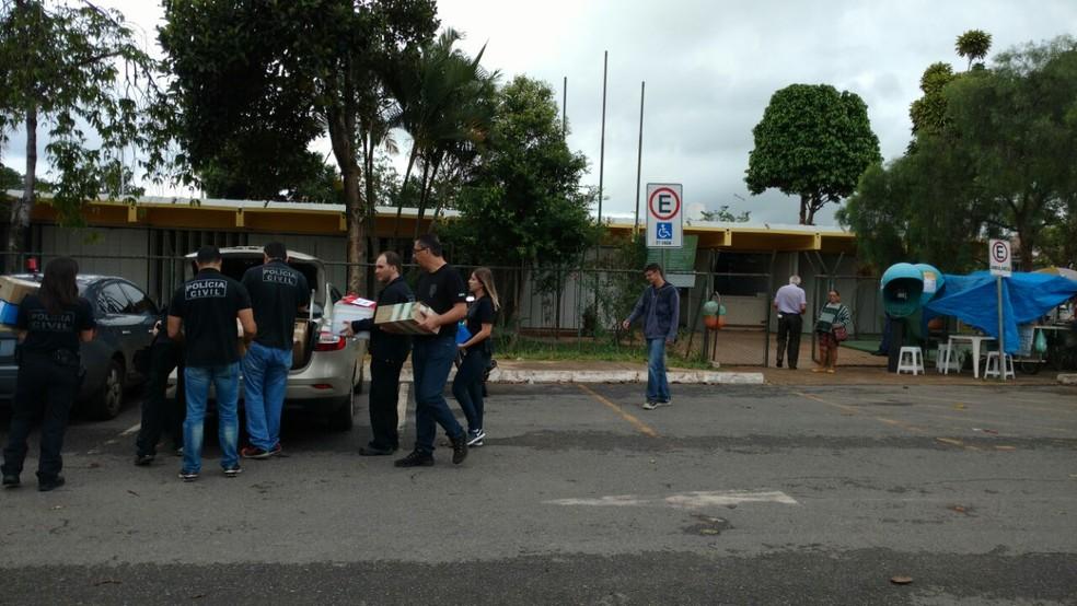 Policiais colocam em carro documentos apreendidos no Centro de Saúde 3 do Guará (Foto: Robson Coutinho/TV Globo)