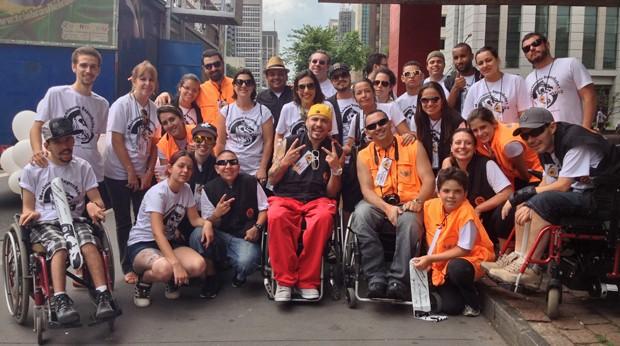 Billy (ao centro, de calças vermelhas), junto com voluntários e participantes. 'Mudou, mas ainda falta muito' (Foto: Cauê Fabiano/G1)